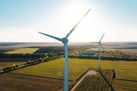 Luftaufnahme der Windmühlen auf dem Feld, aufgenommen von einer Drohne. Erneuerbare Stromquelle. Windkraftanlagen setzen neue Technologie für saubere Energie auf dem Feld ein, Blick auf den Sonnenuntergang mit farbenfroher Dämmerung am Himmel