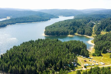 Beautiful lake, mountain peaks in light fog, aerial view from a drone. Coniferous forests on banks of Batak reservoir located in Rhodope Mountains, Bulgaria. Attracts many tourists, fishermen and hunters. Travel and vacation concept Stockfoto