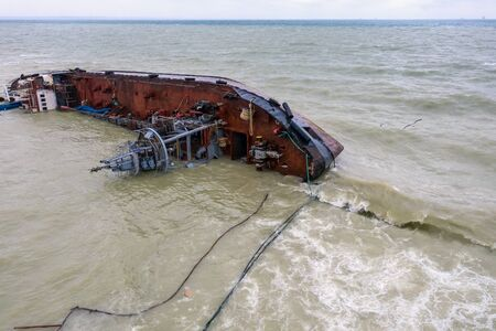 Top view of sinking tanker shot by drone. Inverted tanker wrecked on Black Sea coast of Odessa. Empty tanker leaned to one side and ran aground by during storm with strong wind.
