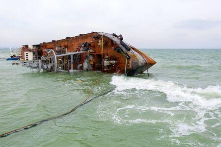 Vue de dessus du navire-citerne en train de couler abattu par drone. Un pétrolier inversé a fait naufrage sur la côte de la mer Noire à Odessa. Le camion-citerne vide s'est penché d'un côté et s'est échoué pendant une tempête avec un vent fort.
