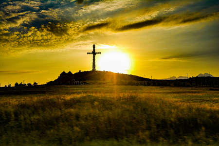 Big cross in the mountains on the background of sunset