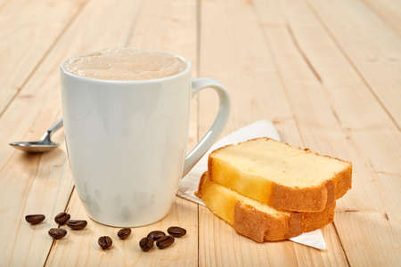Coffee cup with pound cake on wooden table