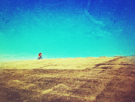 Fietser op dijk met blauwe hemel