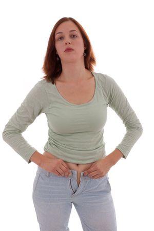 ombligo: Una joven mujer intenta cerrar un pantalones demasiado ajustados  Foto de archivo