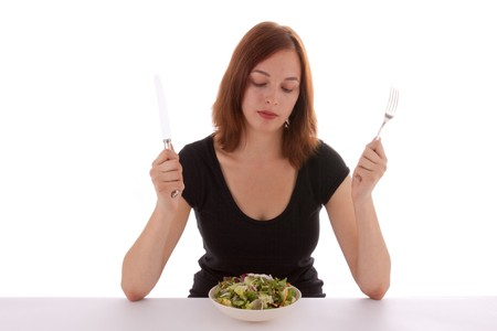 A young woman looks at a plate of salad Stock Photo