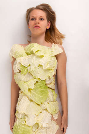 A young woman covered with collard greens