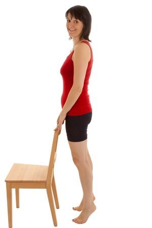 mujeres sentadas: Una joven mujer hacer ejercicios con una silla  Foto de archivo