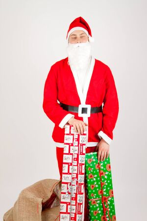 Santa Claus loaded with Christmas gifts photo