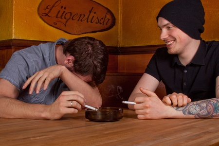 Two friends are sitting in a pub and smoke