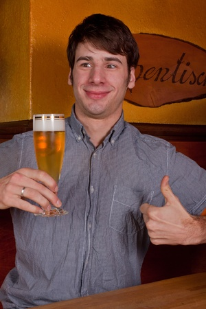 A young man is sitting in pub and drinking a beer photo