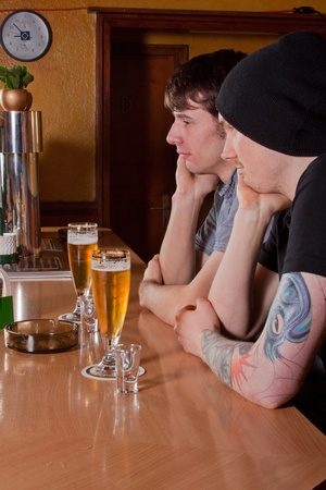 Two friends are sitting in a pub and drinking a beer