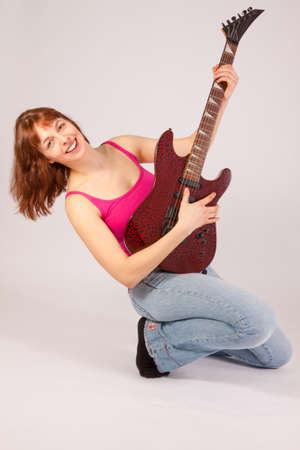 A beautiful young woman is playing a guitar photo