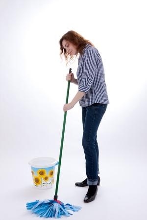 A young woman is wiping the floor with a mop photo