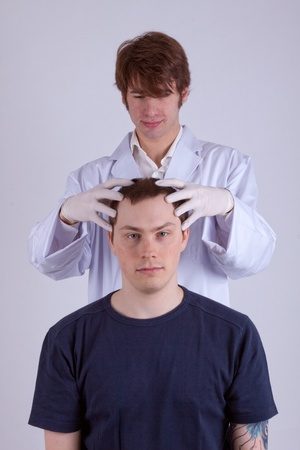 A doctor examines the head of a young man Stock Photo
