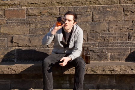 A young man is sitting on a wall drinking beer