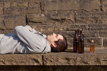 A young man is lying drunk on a bench