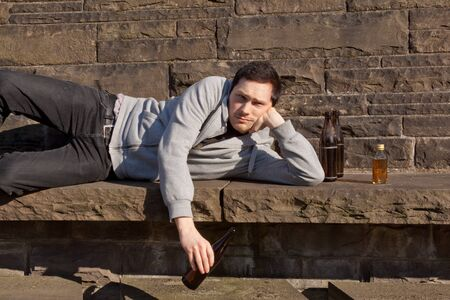 A young guy is lying on a bench drinking beer Stock Photo - 9216592