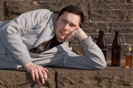 A young man is lying on a bench smoking photo