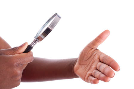 A young black woman is examining her hand with a magnifier Stock Photo - 9409045