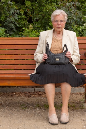 An old lonely woman is sitting on a bench in a park Stock Photo - 9630452
