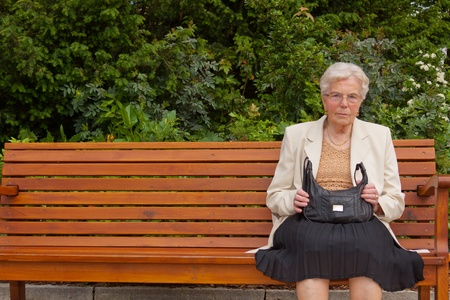 An old lonely woman is sitting on a bench in a park
