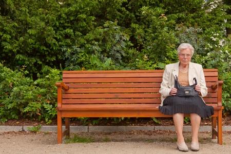 Een eenzame oude vrouw is zittend op een bankje in een park