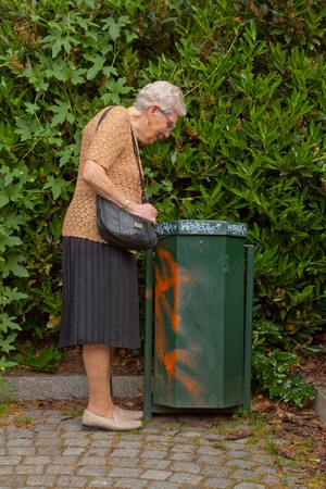 An old lonely woman is looking into garbage can Standard-Bild