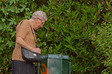 An old lonely woman is looking into garbage can Stock Photo