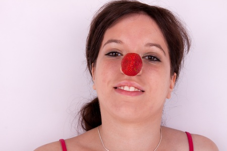 The pretty young woman has a strawberry on the nose