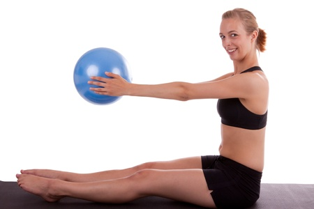 A young woman is doing exercises with a blue ball