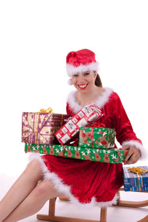 The young Santa Claus is sitting on a little sled and is holding gifts photo
