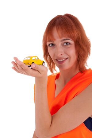 The pretty young girl has a little yellow car in her hand photo