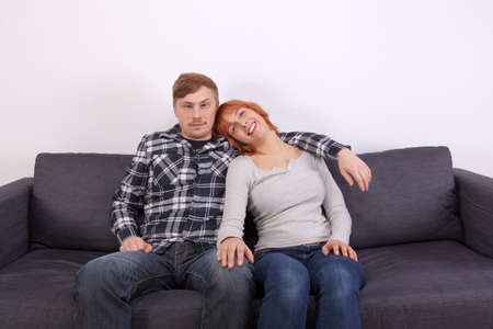 A young couple in love is sitting on the couch photo