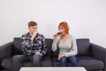 A young couple in love is sitting on the sofa and drinking a glass of wine photo
