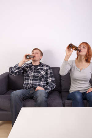 A young couple in love is sitting on the sofa and drinking beer photo