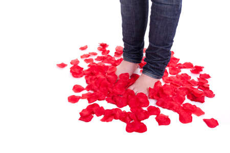 A young beautiful girl is stand in the middle of rose petals photo