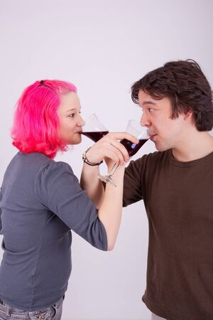 A young man and a young woman are drinking a glass of wine photo