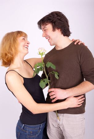 A young man gives his girlfriend a rose photo