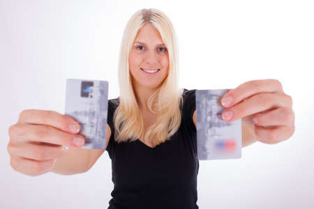 hold ups: A young woman is holding credit cards in her hand