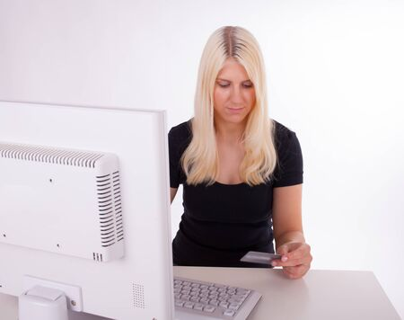 hold ups: A young woman is holding a credit card in her hand while she is typing data in a computer Stock Photo
