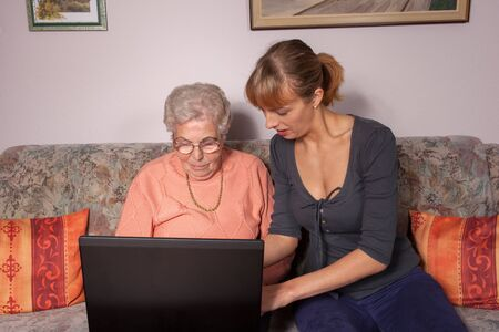 An old woman is a laptop explained by her granddaughter Stock Photo - 13247980