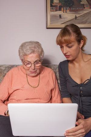 An old woman is a laptop explained by her granddaughter photo