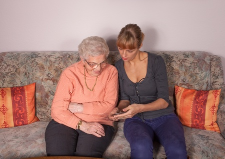 An old woman is a cell phone explained by her granddaughter Standard-Bild