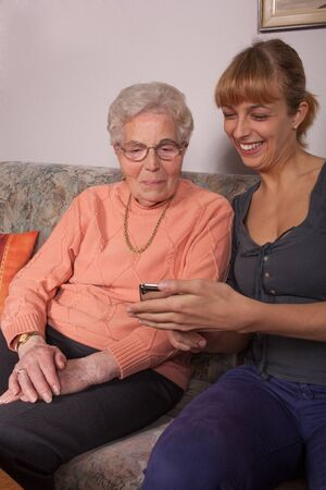 explained: An old woman is a cell phone explained by her granddaughter Stock Photo