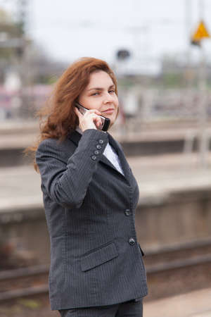 A young business woman is waiting for her train photo