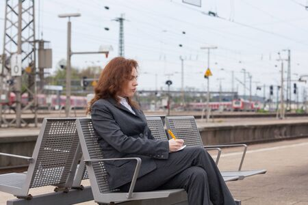 jot: A young business woman is waiting for her train Stock Photo