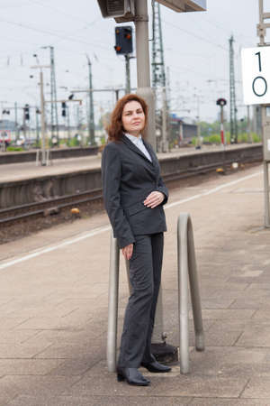 A young business woman is waiting for her train Stock Photo - 13484814