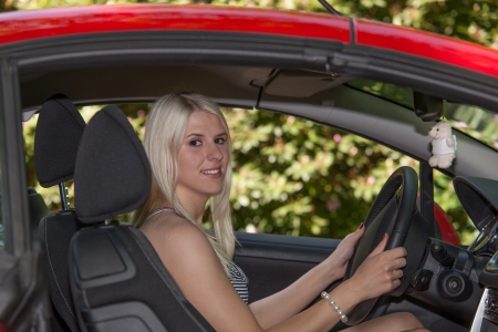 A young girl is driving with her car on vacation photo