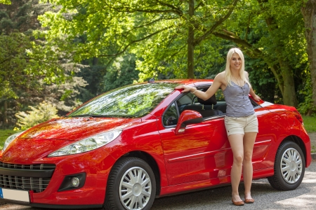 A young girl is standing next to her red car photo