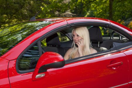 telephoning: The young girl is telephoning in her car